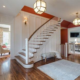 Réalisation d'un grand hall d'entrée tradition avec un mur rouge, un sol en bois brun, une porte simple, une porte en bois brun et un sol marron.