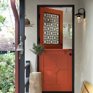 Foto di una porta d'ingresso stile marinaro con una porta olandese e una porta arancione