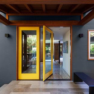 Идея дизайна: входная дверь среднего размера в стиле ретро с синими стенами, полом из керамогранита, поворотной входной дверью, стеклянной входной дверью и серым полом