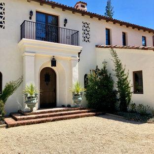 Medelhavsstil inredning av en stor ingång och ytterdörr, med vita väggar, en enkeldörr och mörk trädörr