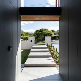 Photo of a contemporary entry hall in Brisbane with black walls and grey floor.