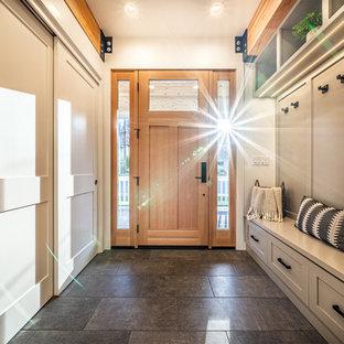 他の地域の中くらいの片開きドアコンテンポラリースタイルのおしゃれな玄関ロビー (グレーの壁、セラミックタイルの床、木目調のドア、グレーの床、表し梁) の写真