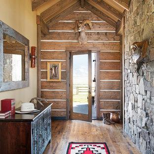 Foto de hall rural con paredes amarillas, puerta simple, puerta de vidrio y suelo de madera en tonos medios