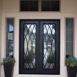 Idée de décoration pour une petit entrée tradition avec béton au sol, une porte double, une porte métallisée et un mur beige.
