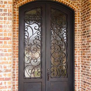 Inspiration för små klassiska ingångspartier, med bruna väggar, betonggolv, en dubbeldörr och metalldörr