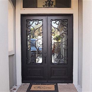 Esempio di una piccola porta d'ingresso classica con pavimento in cemento, una porta a due ante, pareti grigie e una porta in metallo
