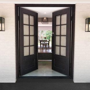 Foto de puerta principal urbana con paredes blancas, suelo de baldosas de porcelana, puerta doble, puerta negra y suelo gris