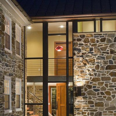 Example of a cottage limestone floor entryway design in Philadelphia with a medium wood front door