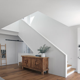 Inspiration for a beach style foyer in Sydney with white walls and medium hardwood floors.
