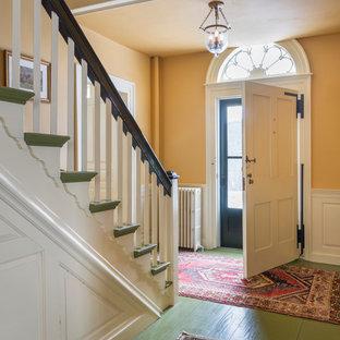 Esempio di un grande ingresso country con pareti gialle, pavimento in legno verniciato, una porta singola e una porta bianca