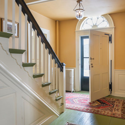 Large country painted wood floor entryway photo in Burlington with yellow walls and a white front door
