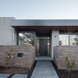 This is an example of a contemporary front door in Canberra - Queanbeyan with a single front door, a black front door and grey floor.
