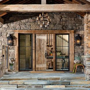 Inredning av en rustik stor ingång och ytterdörr, med en enkeldörr och mellanmörk trädörr