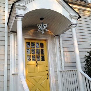 Immagine di una porta d'ingresso classica di medie dimensioni con pareti beige, una porta singola e una porta gialla