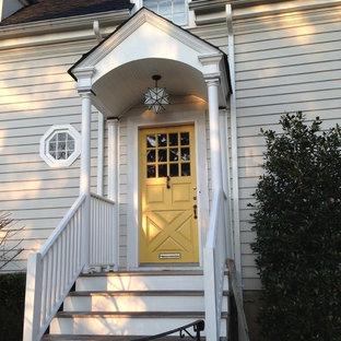 Exempel på en mellanstor klassisk ingång och ytterdörr, med beige väggar, en enkeldörr och en gul dörr