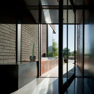Modelo de puerta principal moderna, grande, con paredes grises, suelo de terrazo, puerta pivotante y puerta metalizada