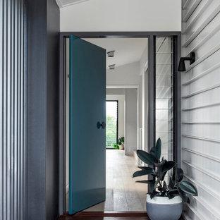 Ispirazione per una grande porta d'ingresso design con pareti bianche, parquet chiaro, una porta a pivot e una porta verde