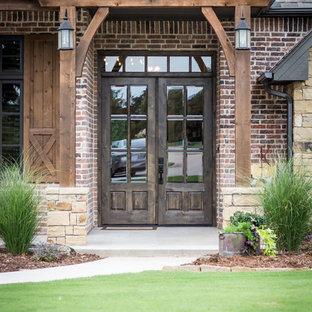 Cette photo montre une porte d'entrée nature de taille moyenne avec un mur rouge, béton au sol, une porte double, une porte en bois foncé et un sol gris.