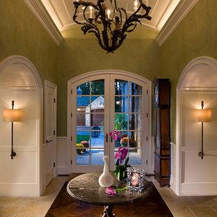 Réalisation d'un hall d'entrée tradition de taille moyenne avec un mur vert, un sol en bois foncé, une porte simple, un sol marron, un plafond à caissons et boiseries.