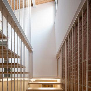 Ispirazione per una piccola scala sospesa design con pedata in legno e nessuna alzata