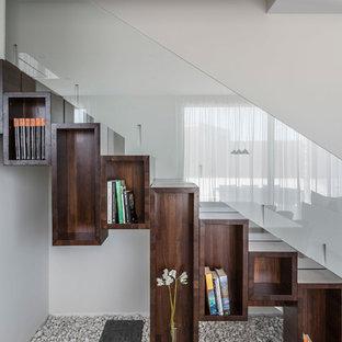 Diseño de escalera recta, moderna, con escalones de madera, contrahuellas de madera y barandilla de vidrio