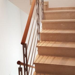 Imagen de escalera en L, retro, de tamaño medio, con escalones con baldosas, contrahuellas con baldosas y/o azulejos y barandilla de metal