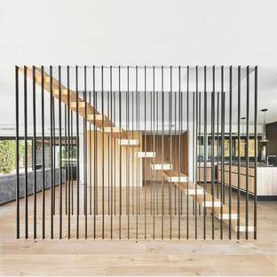 Ejemplo de escalera suspendida, minimalista, sin contrahuella, con escalones de madera