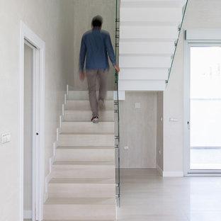 Modelo de escalera en U, contemporánea, grande, con escalones con baldosas, contrahuellas con baldosas y/o azulejos y barandilla de vidrio
