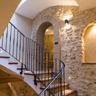 Ejemplo de escalera en U, rústica, grande, con escalones con baldosas, contrahuellas de terracota y barandilla de metal