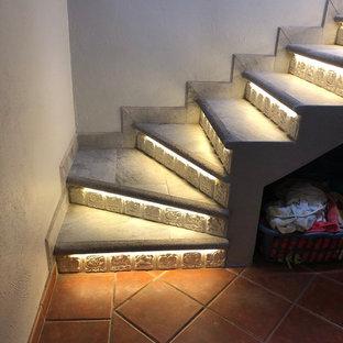 Imagen de escalera en U, minimalista, de tamaño medio, con escalones con baldosas, contrahuellas con baldosas y/o azulejos y barandilla de metal
