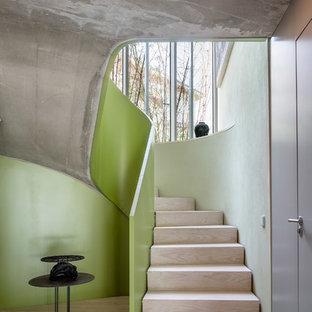 Imagen de escalera curva, actual, con escalones de madera y contrahuellas de madera