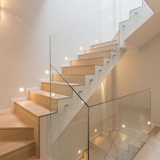 Foto de escalera en U, contemporánea, con escalones de madera, contrahuellas de madera y barandilla de vidrio