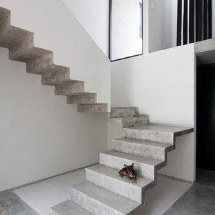"""Immagine di una scala a """"L"""" minimalista con pedata in cemento e alzata in cemento"""