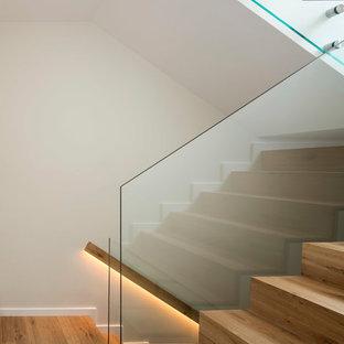 Foto de escalera en U, escandinava, de tamaño medio, con escalones de madera, contrahuellas de madera y barandilla de vidrio