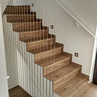 他の地域のタイルの地中海スタイルのおしゃれな階段 (タイルの蹴込み板、ワイヤーの手すり) の写真
