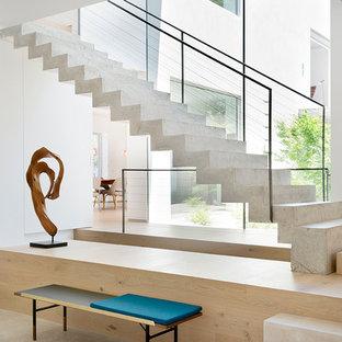マドリードのコンクリートのコンテンポラリースタイルのおしゃれな直階段 (コンクリートの蹴込み板、ワイヤーの手すり) の写真