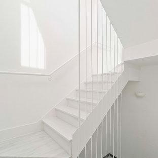 Imagen de escalera en U, actual, pequeña, con escalones de mármol, contrahuellas de mármol y barandilla de metal