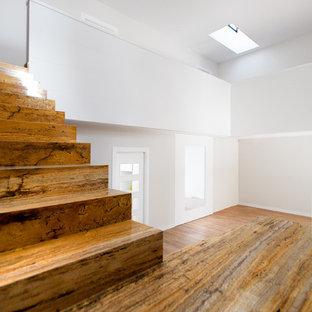 マドリードのトラバーチンのコンテンポラリースタイルのおしゃれな折り返し階段 (トラバーチンの蹴込み板、ガラスの手すり) の写真