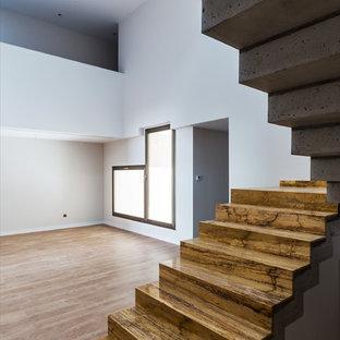 Imagen de escalera en U, actual, con escalones de travertino, contrahuellas de travertino y barandilla de vidrio