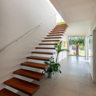 Diseño de escalera suspendida, contemporánea, sin contrahuella, con escalones de madera y barandilla de metal