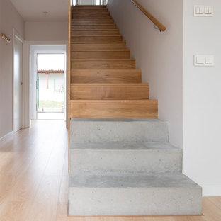 他の地域のコンクリートのコンテンポラリースタイルのおしゃれな直階段 (コンクリートの蹴込み板、木材の手すり) の写真