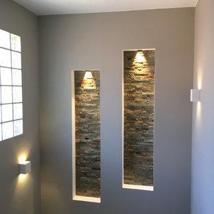 На фото: п-образная лестница среднего размера в стиле модернизм с ступенями из травертина, подступенками из травертина и перилами из смешанных материалов