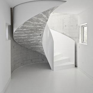 Immagine di una scala curva contemporanea di medie dimensioni con pedata in cemento e alzata in cemento