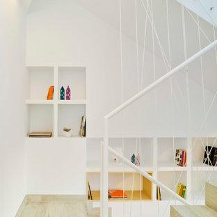 Modelo de escalera en U, contemporánea, con escalones de madera, contrahuellas de madera y barandilla de metal