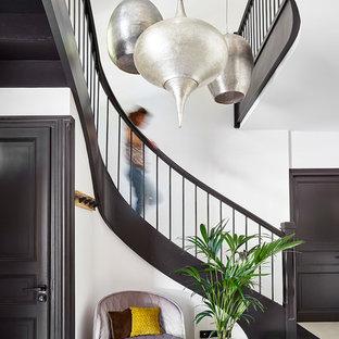 Ejemplo de escalera curva, mediterránea, con barandilla de madera