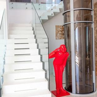 Diseño de escalera en L, actual, de tamaño medio, con escalones de acrílico