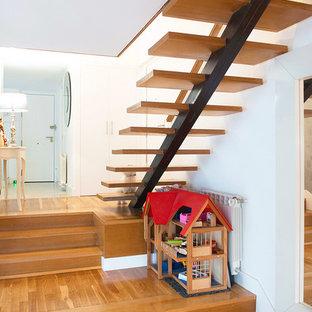 Ispirazione per una scala sospesa minimalista con pedata in legno e parapetto in vetro