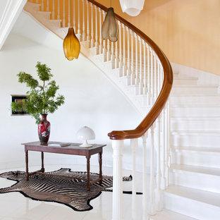 Esempio di una scala curva boho chic con pedata in legno verniciato, alzata in legno verniciato e parapetto in legno