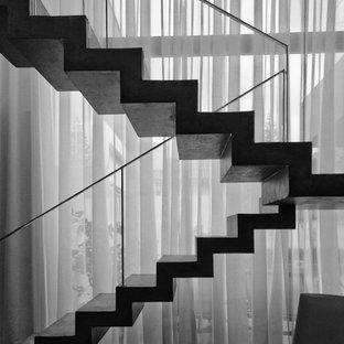 他の地域の広いコンクリートのモダンスタイルのおしゃれな折り返し階段 (コンクリートの蹴込み板、金属の手すり) の写真