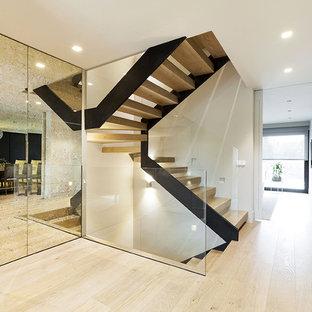 Ejemplo de escalera en U, actual, sin contrahuella, con escalones de madera y barandilla de vidrio